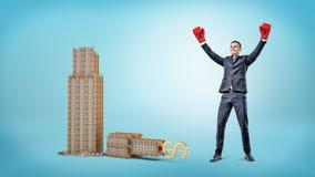 在拳击手套的一个愉快的商人在与一个金黄美元的符号的小打破的企业大厦附近站立在它的上面 免版税库存图片
