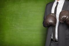 在拳击手套的商人在黑板 免版税库存照片