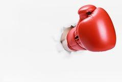 在拳击手套的手打破了纸墙壁 库存图片