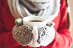 在拿着一个杯子用热的咖啡的小野鸭手套的妇女手 免版税库存照片