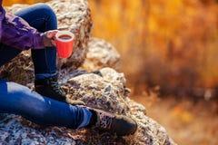在拿着一个杯子茶的山女孩顶部 免版税库存照片