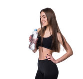 在拿着一个瓶在白色背景的纯净的水的锻炼以后的正面女性健身模型 免版税库存图片