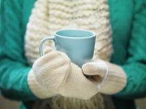 在拿着一个舒适杯子用热的可可粉、茶或者咖啡的白色羊毛手套的妇女手 冬天和圣诞节时间概念 免版税库存图片