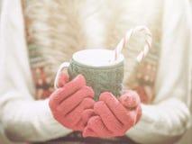 在拿着一个舒适杯子用热的可可粉的羊毛红色手套的妇女手、茶或者咖啡和棒棒糖 冬天和圣诞节概念 免版税库存图片