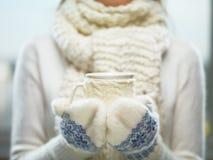 在拿着一个舒适被编织的杯子用热的可可粉、茶或者咖啡的白色和蓝色手套的妇女手 冬天和圣诞节时间概念 免版税库存图片