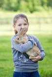 在拿着一只活兔子的街道上的小女孩 免版税库存图片