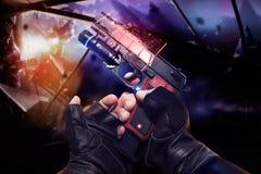 在拿着一把红色霓虹给充电的手枪的黑手套的手 免版税图库摄影