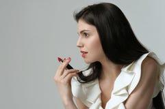 在拿着一支唇膏l一个俏丽的女孩的档案的画象 库存照片