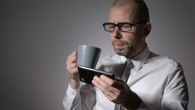 在拿着一杯咖啡或茶的白色衬衣的典雅的商人在手上 使用a,人做了一个断裂在工作, 影视素材