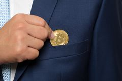 在拿着一枚金黄位硬币的衣服的商人 库存图片