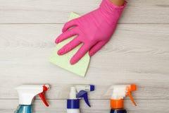 在拿着与瓶的桃红色橡胶手套的手尘土餐巾洗涤剂 库存图片