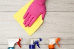 在拿着与瓶的桃红色橡胶手套的手尘土餐巾洗涤剂 图库摄影