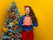 在拿着书的圣诞树妇女附近的微笑的时髦妇女 图库摄影