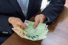 在拿着五十和一百欧洲票据笔记的衣服的手 免版税图库摄影