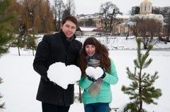 在拿着从雪的爱人和女孩的夫妇心脏 免版税库存照片