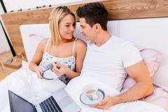 在拿着咖啡的爱的夫妇,当在床上时 库存照片