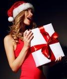 在拿着圣诞节礼物的一件红色礼服的性感的白肤金发的圣诞老人 免版税库存图片