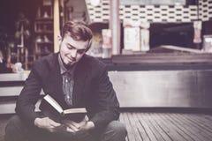 在拿着圣经的一个人的特写镜头在商城,相信 免版税库存照片
