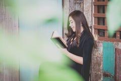 在拿着圣经的一名年轻亚裔妇女的特写镜头和祈祷 免版税库存照片
