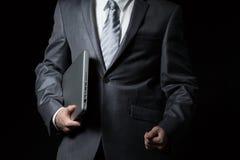 在拿着在一条胳膊的灰色衣服的商人膝上型计算机 免版税库存照片