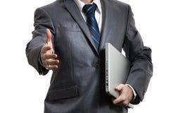 在拿着在一条胳膊的灰色衣服的商人膝上型计算机 图库摄影