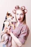 在拿着在她的胳膊的惊奇的画报性感的白肤金发的年轻美丽的妇女的特写镜头一条狗看照相机画象 免版税图库摄影