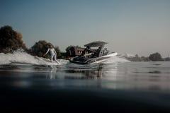在拿着在汽艇的wakeboard的白肤金发的女孩骑马一条绳索 免版税库存图片