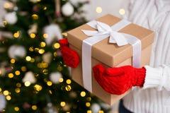 在拿着在装饰的圣诞节的手套的女性手礼物盒 免版税库存照片