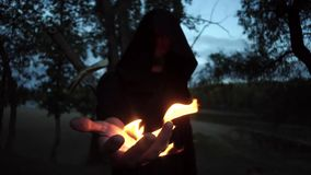 在拿着幻想中世纪礼服的斗篷的神奇witcher一个火人 万圣节 影视素材