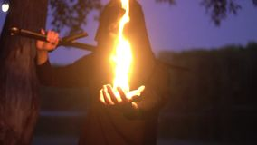 在拿着幻想中世纪礼服的斗篷的神奇witcher一个火人 万圣节 股票视频