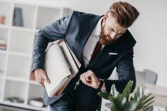 在拿着文件和文件夹的衣服的商人在办公室 免版税图库摄影