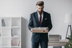 在拿着文件和文件夹的衣服的商人在办公室 免版税库存照片