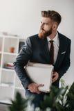 在拿着文件和文件夹的衣服的商人在办公室 库存照片