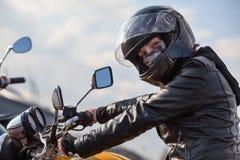 在拿着方向盘和看照相机,白种人妇女的黑成套装备的摩托车驾驶员 免版税图库摄影