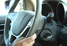 在拿着方向盘的汽车的司机 免版税库存照片