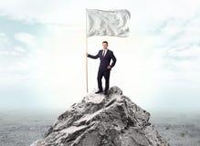 在拿着旗子的上面的商人山的 库存例证