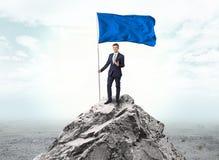 在拿着旗子的上面的商人山的 向量例证