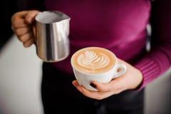 在拿着有拿铁艺术的紫色衬衣的Barista一个咖啡杯 免版税库存图片
