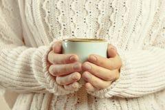 在拿着有热的饮料的毛线衣的女性手杯子 库存照片