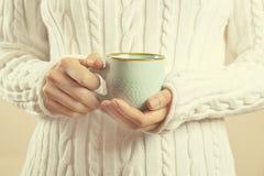 在拿着有热的饮料的毛线衣的女性手杯子 免版税库存图片
