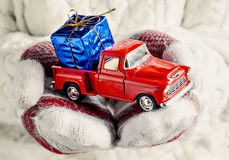 在拿着有礼物的蓝色bo的手套的手一辆玩具红色葡萄酒汽车 免版税图库摄影