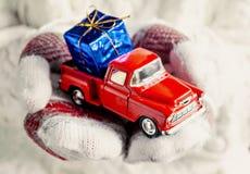 在拿着有礼物的蓝色bo的手套的手一辆玩具红色葡萄酒汽车 库存图片