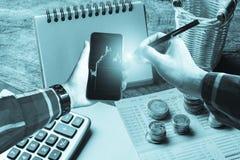 在拿着有金币的, calcul的行家衬衣的手智能手机 免版税库存图片