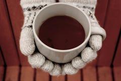 在拿着杯子热的红茶的羊毛温暖的手套的手反对未聚焦的橙色长凳顶视图 免版税库存照片