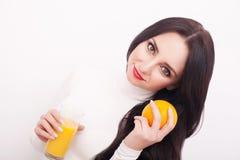 在拿着杯橙汁的白色背景的运动的妇女 免版税库存照片