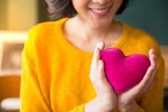 在拿着桃红色心脏的黄色sweather的妇女手 图库摄影