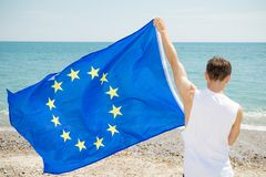 在拿着欧盟旗子的海滩的白种人男性 图库摄影