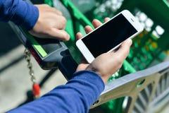在拿着流动智能手机的人的特写镜头手中在购物期间 库存图片