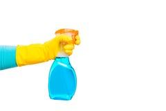 在拿着清洗的玻璃的黄色手套的手一朵浪花 图库摄影