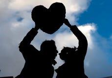 在拿着爱心脏的剪影的有吸引力的夫妇 图库摄影